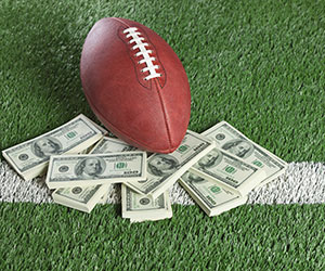football stacked on money